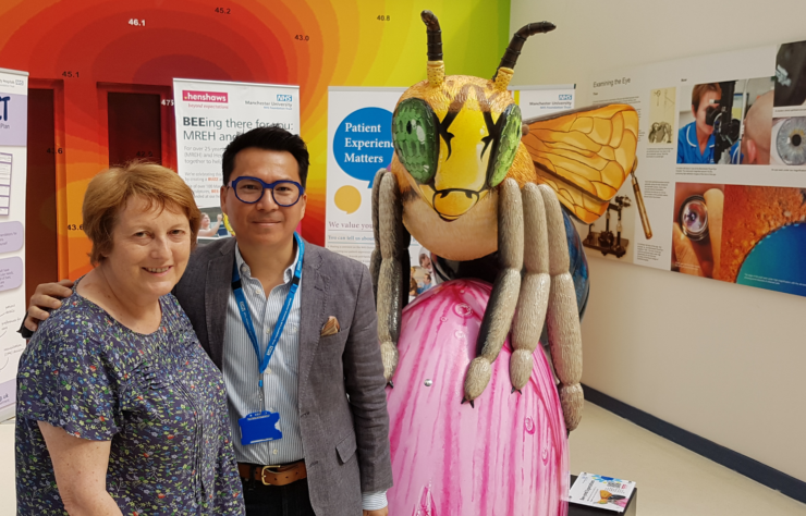 Glaucoma patient Pam stood with Consultant Ophthalmic Surgeon, Leon Au, after her surgery. Stood in front of a Manchester bee smiling inside the Manchester Royal Eye Hospital